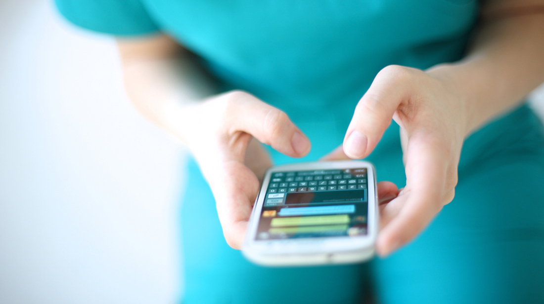 nurse sending message via smartphone